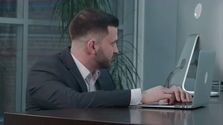 tartışıyor : Attractive caucasian businessman using laptop, while talking with partner at workplace