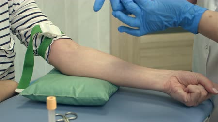 take blood : Nurse collecting blood from patient vein Stock Footage