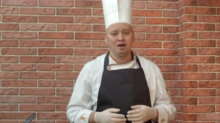 büszke : Smiling cook standing in the kitchennd talking to the camera about dish he is going to prepare