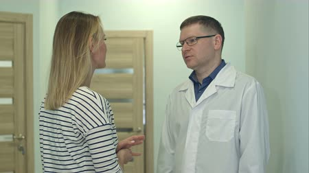 подопечный : Male doctor talking to young woman patient in the hospital hall