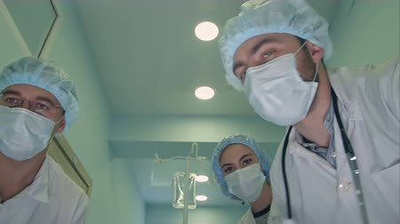 surgical light : Group of surgeons looking down at patient on the way to operation room Stock Footage