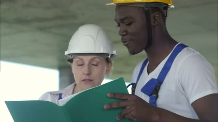 строительные леса : Afro-american architect and female technician at construction site reviewing office blueprints