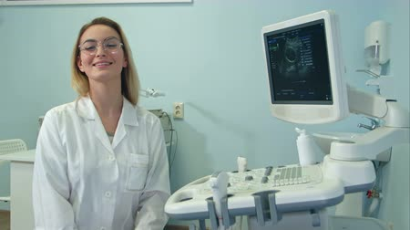obstetra : Smiling female doctor in glasses looking into the camera in ultrasound room