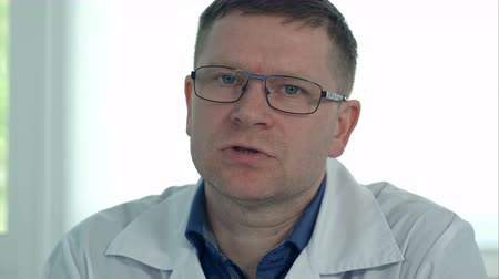affidabile : Male doctor in glasses talking to the camera