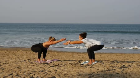 Teacher and student doing yoga at Sunrise