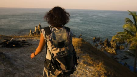 climber rock : Cheering young woman backpacker at sunrise seaside mountain peak