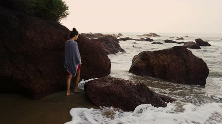 Венера : Young playful woman walking between rocks on beachside and has fun