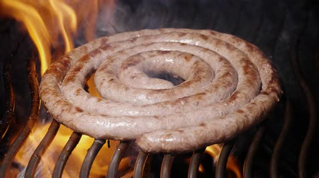 baharatlı alman sosisi : Slow motion shot of the delicious homemade meat sausage frying on the grill with flames and smoke