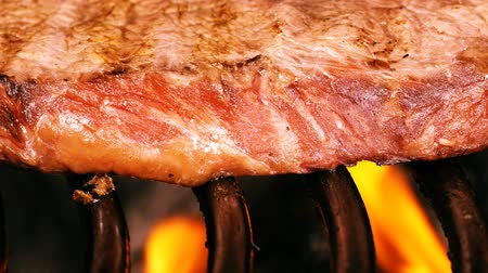 fileto : UHD shallow DOF slow dolly shot of the juicy marbled beef steak on a barbecue grill Stok Video