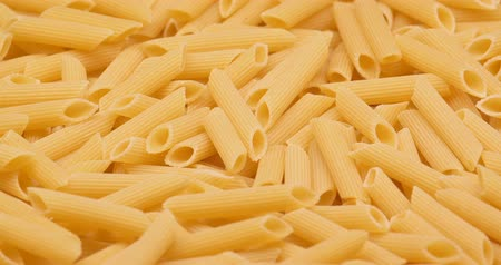 лапша : C4K macro of the dry Penne pasta on a rotating stand Стоковые видеозаписи