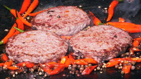 marmorizado : Slow motion shot of the delicious premium beef burgers are being fried with hot red peppers