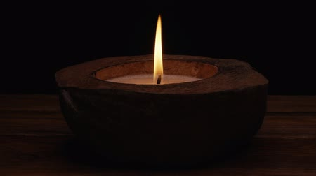 пламя : UHD low key closeup shot of the spa coconut candle Стоковые видеозаписи
