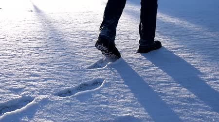 Man goes snowy meadow legs are visible. Footprints in snow.