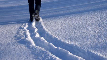 Man goes snowy meadow, are seen only by foot. Footprints in snow.