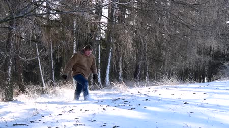 A man comes out of the forest and goes into the field with snow.