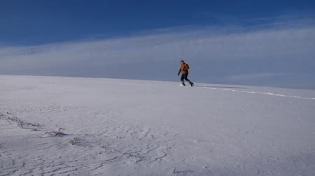 The man running the snowy plains and looked behind him.