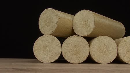 briquette : Wood sawdust briquettes straightened, black background. Alternative fuel, bio fuel. Slider shot_1 Stock Footage