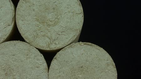 preslenmiş : Wood sawdust briquettes straightened, black background. Alternative fuel, bio fuel. Slider shot