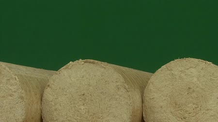 briquettes : Wood sawdust briquettes straightened, green screen background. Alternative and bio fuel. Slider shot Stock Footage