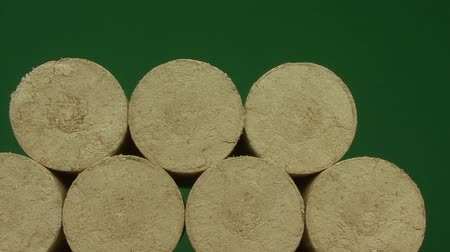 briquettes : Wood sawdust briquettes straightened, green screen background. Alternative fuel, bio fuel. Slider shot. Stock Footage