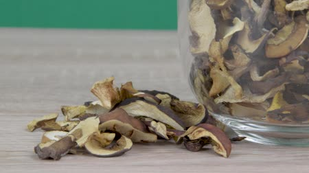 Dried mushrooms on a wooden table and in a glass mug. Green background. Slider shot