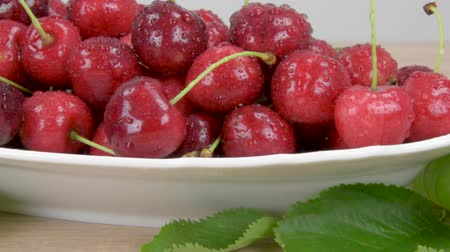 Ripe red cherry on a white plate on a wooden table, Around the green leaves. Slider shot