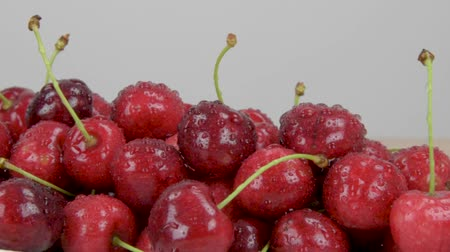 Ripe red cherries. Drops of water on cherries. White background. Slider shot. Стоковые видеозаписи