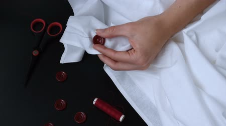 sem camisa : Female hands sewing red button on white fabric