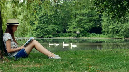 bird learning : Girl sitting in the park near the lake under the tree and reading a book. Stock Footage