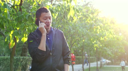 haver : Young Asian handsome man talking on the phone in the summer sunny Park