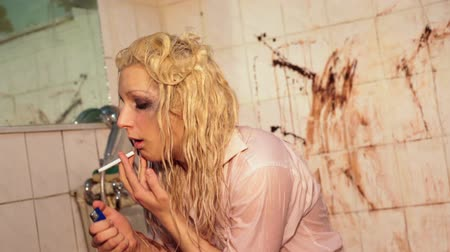 repce : hopeless blond girl eagerly smokes cigarette in dirty bathroom. depression Stock mozgókép