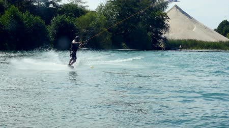 A wakeboarder in helmet slides over the water in a cable park. Slow motion Wideo