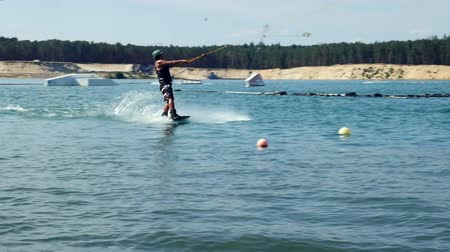 Wakeboarder Ride On Cable Wake board In slow motion on water.