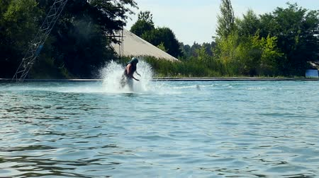 Wakeboarder crashes On Cable Wake board into a water with splashes. slow motion Vídeos
