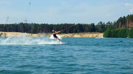 Beautiful and professional wakeboarder trains on wake board in summer cable park