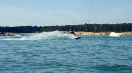 A Man Rides His Wakeboard At A Cable Park, Slow Motion. wake boarding tricks.