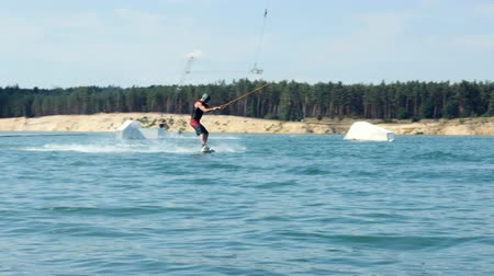 Wakeboarder Sportsman training wake boarding tricks in cable wake park Wakeboard