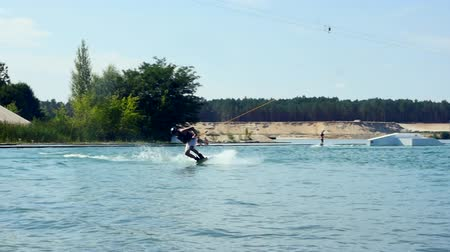 Wakeboard sportsman training wake boarding tricks in cable wake park Slow Motion