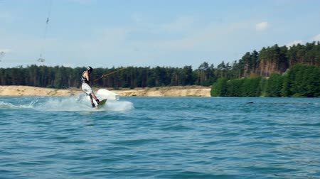 Young man Riding Wakeboard On Lake. Looks at camera training wake boarding stunt