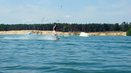 Jump With Wake-board In Cable Park. Wakeboarder surfing athlete water Slow Mo