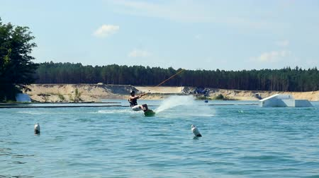 Young man Riding Wakeboard On Lake Park. Moving into camera and crash into water Vídeos