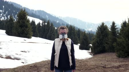Girl in gasmask stand in nature. winter gas mask mountains