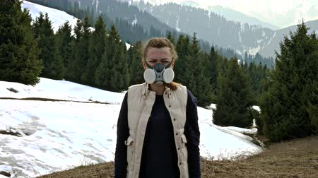 Girl in gas mask standing in nature and looking at the camera