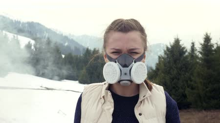 Portrait of a girl in gas mask looks at camera in nature