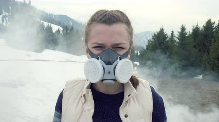 Smoke around. Teen in gas mask looks at camera in nature.