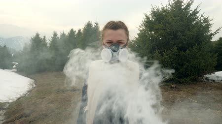 Girl in gas mask looks straight through the smoke