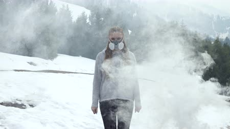 Woman in respirator in nature in smoke
