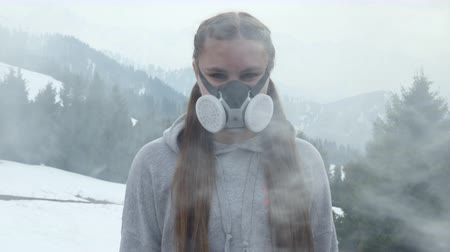bad ecology : girl in the smoke in a gas mask in the mountains Stock Footage