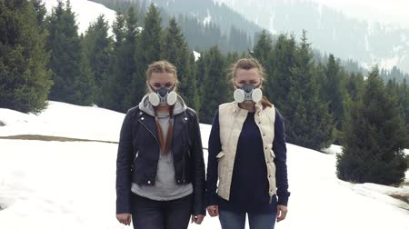 two young girls in a gas mask in the smoke in the mountains