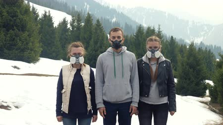 Three youngers in a gas mask in nature